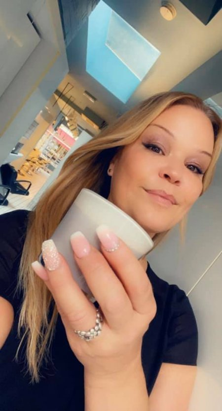 Girl with long blonde hair drinking a coffee in a white cup