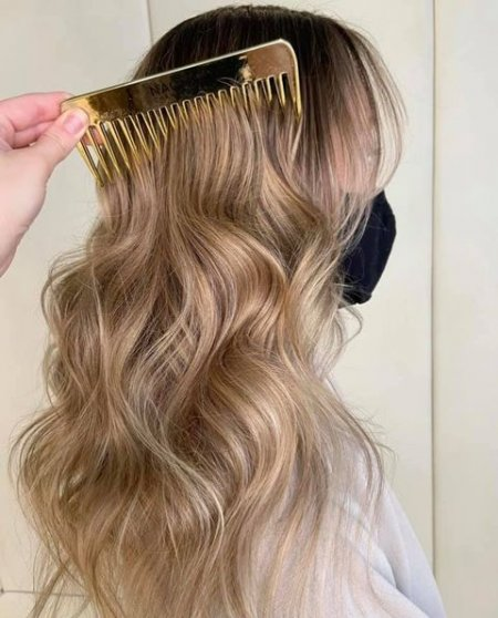 Long hair being combed with a golden comb at the klink salon London