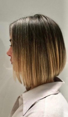 Girl standing on the side with a bob cut by Jenni at the klinik salon