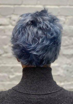 Girl with short blue hair and a grey cardigan at the klinik salon