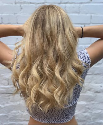 Girl with long blonde hair from behind holding uo her hair showing off a balayage.