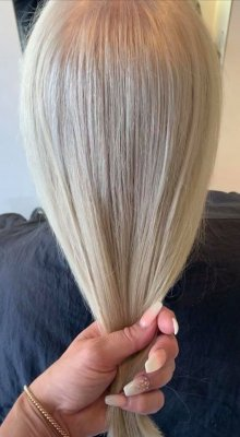 hand holding a natural white hair beng coloured at the klinik hairdressing London