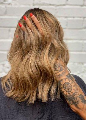A tatooed hand running trough a freshly caramel coloured hair done by Cinzia at the klinik salon