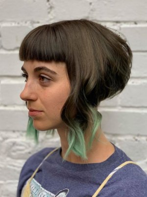 Girl with a disconnected bob with long pieces at the front and shaved back with green tips at the klinik salon London