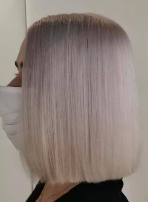 Icy white hair on a shoulder length bob on a lady wearing a face mask.