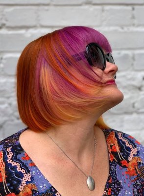 A girl with a multi coloured bob in tones of copper, pink, purple and yellow, wearing sunglasses at the klinik salon London