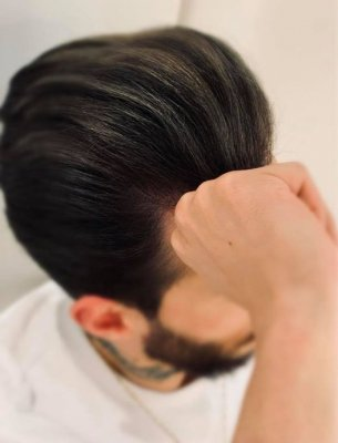 A guy sitting in a white tshirt showing off his slate grey highlights at the klinik salon London