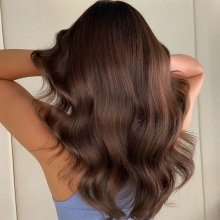 Girl holding her newly coloured brown hair at the klinik salon London